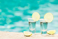Tequila shots with lime on blue background Royalty Free Stock Photography