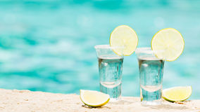 Tequila shots with lime on blue background Royalty Free Stock Photos