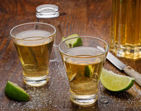 Tequila Shots. Shots of tequila on a wooden bar top with lemon and salt Stock Photos