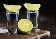 Tequila silver shots with lime slices and salt on wooden board Royalty Free Stock Photos