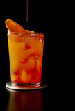 Tequila sunrise. Pouring a tequila sunrise cocktail decorated with an orange slice royalty free stock image