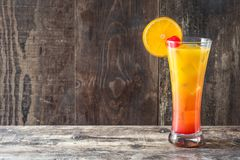 Tequila sunrise cocktail in glass on wood. En table. Copyspace royalty free stock images