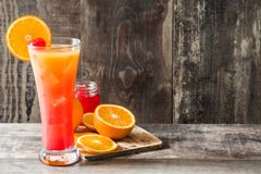 Tequila sunrise cocktail in glass on wooden table. Copyspace royalty free stock image