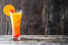 Tequila sunrise cocktail in glass on wooden table. Copyspace royalty free stock images