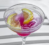 Tequila sunrise cocktail in a transparent glass with ice and slices of lemon, liquor Stock Image