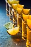 Tequila und Kalk auf Glastisch Stockfotografie