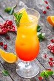 Tequila wschodu słońca koktajl z mennicą, pomarańcze i granatowem w wysokim szkle na drewnianym tle, Lato napoje i alkoholiczny c Fotografia Royalty Free