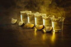 Tequilaen i skottexponeringsglas med limefrukt och saltar Royaltyfri Fotografi