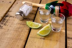 Tequilaschüsse mit Kalkscheiben auf Tabelle mit Dekorationen stockfotos
