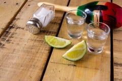 Tequilaschoten met kalkplakken op lijst met decoratie stock foto's