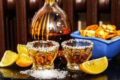 Tequilaschoten met zout, citroen en snacks stock fotografie