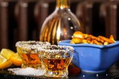 Tequilaschoten met zout, citroen en snacks stock foto's