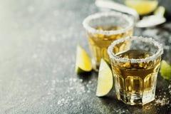 Tequilaskott med limefrukt och hav som är salt på den svarta tabellen royaltyfri fotografi