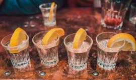 Tequilaskott med limefrukt och hav som är salt på den svarta tabellen, selektiv fokus arkivfoto