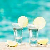 Tequilaskott med limefrukt på blå bakgrund Royaltyfria Foton