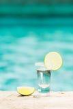 Tequilaskott med limefrukt på blå bakgrund Royaltyfri Foto
