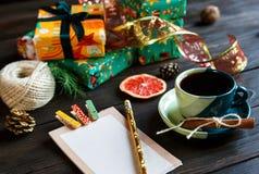Teraźniejszość dla przyjaciół i rodziny w papierze pomarańczowym i zielonym, notepad, filiżanka kawy na drewnianym tle na zakupy zdjęcie stock