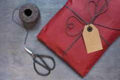Teraźniejszość w czerwieni paczce z etykietką i retro nożycami Zdjęcia Royalty Free
