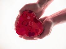 Teraźniejszość w mężczyzna ` s rękach w postaci kierowego białego tła Czerwony Kierowy symbol z ręką teraźniejszy dzień valentine Obrazy Royalty Free