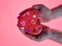 Teraźniejszość w mężczyzna ` s rękach w postaci serce menchii tła Czerwony Kierowy symbol z ręką teraźniejszy dzień valentine s Zdjęcia Stock