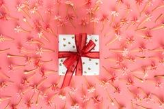 Teraźniejszy pudełko z czerwonym łękiem na różowym małym kwiatu tle Fotografia Stock
