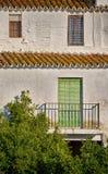 Teracotta ha piastrellato, casa mediterranea bianca con le finestre cieche e di legno verde pallide immagini stock