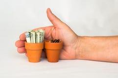 Terakotowy garnek z staczający się w górę pieniądze, zmiany i ręki, za nim Zdjęcia Royalty Free