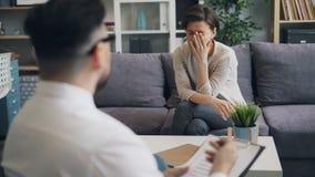 Terapeut f?r ung man som talar till den stressade kvinnan som fr?gar fr?gan som i regeringsst?llning arbetar arkivfilmer