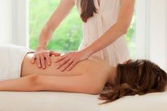 Terapeut som baksidt ger massage Arkivbilder