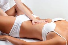 Terapeut som gör buk- massage på kvinna royaltyfri foto