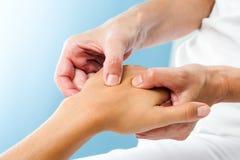 Terapeut som gör massage på den kvinnliga handen royaltyfri fotografi