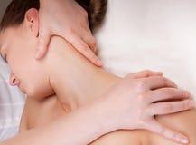 Terapeut som gör massage på en kvinnas hals Arkivbild