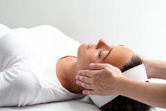 Terapeut som gör reiki med händer bredvid kvinnas huvud Arkivfoto