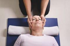 Terapeut som gör reikiterapi till den höga kvinnan Arkivfoto