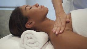 Terapeut som masserar skuldror av den afrikanska kunden i brunnsortmitt stock video