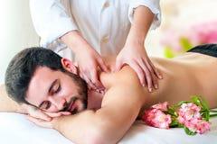 Terapeut som tillbaka gör massage på ung man royaltyfri foto