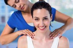 Terapeut som tillbaka gör massage till hennes patient arkivfoto