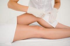 Terapeut som vaxar kvinnas ben på brunnsortmitten Arkivfoton