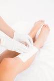 Terapeut som vaxar kvinnas ben på brunnsortmitten Arkivfoto