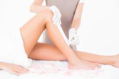 Terapeut som vaxar kvinnas ben på brunnsortmitten Royaltyfri Foto