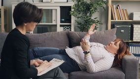 Terapeuta amigável que fala para virar a menina obeso que encontra-se no sofá que discute o problema vídeos de arquivo