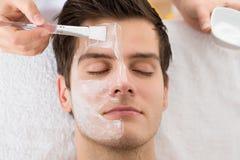 Terapeuta Applying Face Mask a servir Imágenes de archivo libres de regalías