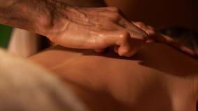 Terapeuta ascendente cercano del masaje de las manos que hace masaje remediador de nuevo a un hombre adulto almacen de metraje de vídeo