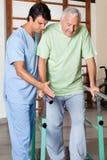 Terapeuta Assisting Senior Man a caminar con Fotografía de archivo