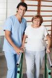 Terapeuta Assisting Senior Woman a caminar con Foto de archivo