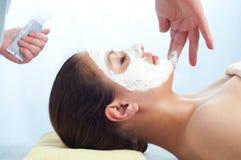 Terapeuta da massagem que aplica o creme antienvelhecimento Fotos de Stock