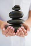 Terapeuta de la belleza que sostiene la pila de piedras para el masaje fotos de archivo