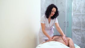 Terapeuta de sexo femenino hermoso que da masajes a hombros y al abdomen del cliente masculino metrajes