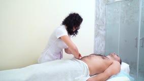 Terapeuta de sexo femenino hermoso que hace masaje de relajación en el abdomen masculino en salón del balneario metrajes