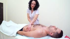 Terapeuta de sexo femenino joven que hace masaje de relajaci?n en el abdomen del cliente masculino en balneario almacen de video